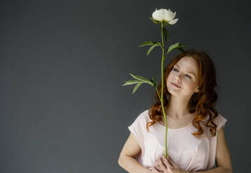 Portrait of redheaded woman with white peony - KNSF06497