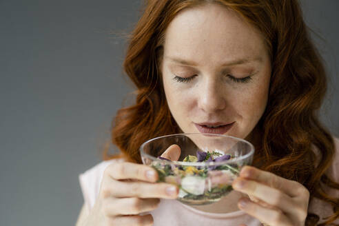Portrait of redheaded woman smelling blossoms in glass bowl - KNSF06500