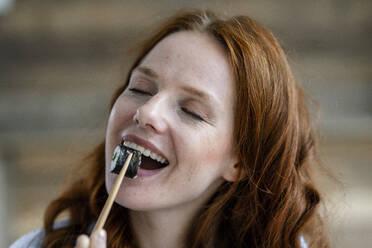 Portrait of happy redheaded woman eating sushi - KNSF06509