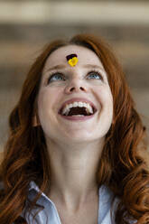 Portrait of redheaded woman looking at violet on her forehead - KNSF06512