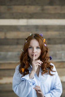 Portrait of redheaded woman with blossoms in hair and finger on her mouth - KNSF06515