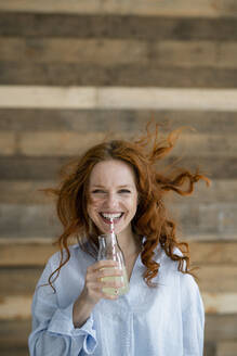 Portrait of laughing redheaded woman with blowing hair drinking lemonade - KNSF06518