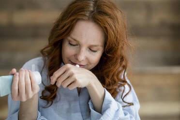 Portrait of redheaded woman smelling cream - KNSF06521