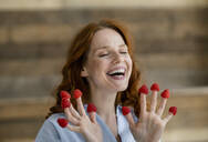 Portrait of laughing redheaded woman with raspberries on her fingertips - KNSF06524
