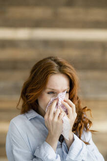 Redheaded woman blowing nose - KNSF06530