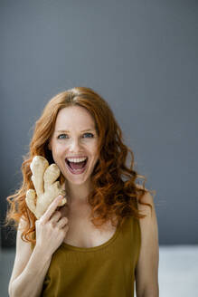 Portrait of excited redheaded woman with ginger root - KNSF06533