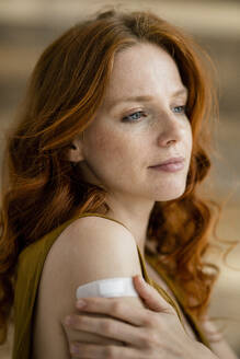 Portrait of redheaded woman with band-aid on her shoulder - KNSF06536