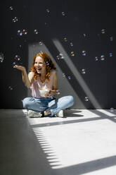 Portrait of happy woman sitting on the floor with coffee bowl touching soap bubbles - KNSF06539