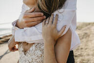 Close-up of affectionate bride and groom hugging outdoors - LHPF00787