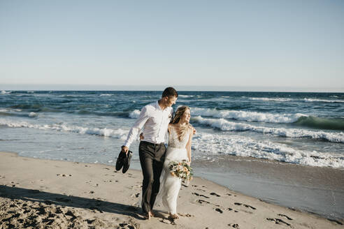 Bride and groom walking on the beach - LHPF00811