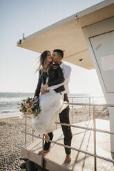 Happy bride and groom at lifeguard hut on the beach at sunset - LHPF00817