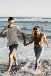 Happy young couple running at the seashore - LHPF00832