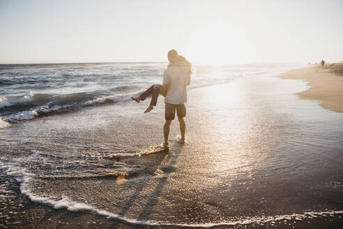 Happy young man carrying girlfriend at the seashore at sunset - LHPF00838