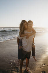 Portrait of happy young man carrying girlfriend piggyback on the beach at sunset - LHPF00841