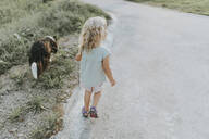 Rear view of girl going walkies with dog ona country lane - DWF00490