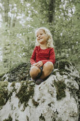 Blond girl sitting on rock in the forest - DWF00496