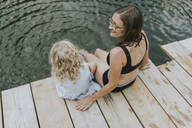 Mother and daughter sitting on jetty at a lake - DWF00499