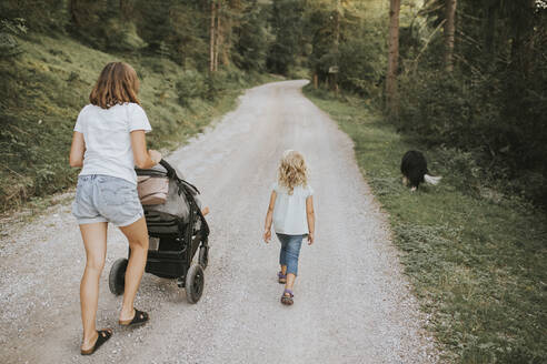 Mother with daughter, stroller and dog walking on forest path - DWF00508