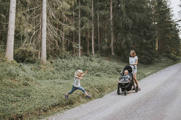 Mother with daughter and baby in stroller in forest - DWF00511