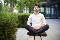 Businessman doing yoga on a bench in the city - PNEF02036