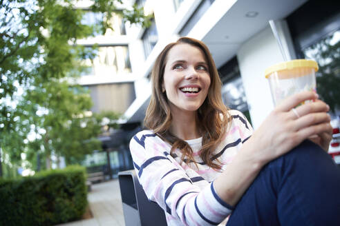 Smiling woman having a break in the city holding a cup - PNEF02039