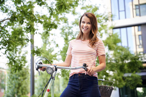 Portrait of smiling woman with bicycle in the city - PNEF02042