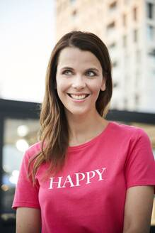 Portrait of happy woman wearing pink t-shirt in the city - PNEF02069