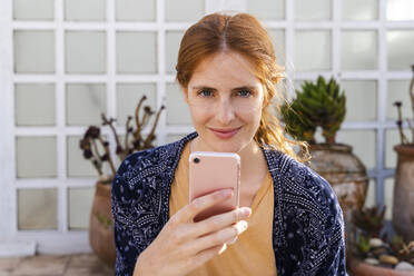 Portrait of smiling redheaded young woman with cell phone on terrace - AFVF03954