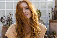 Portrait of smiling redheaded young woman on terrace - AFVF03957