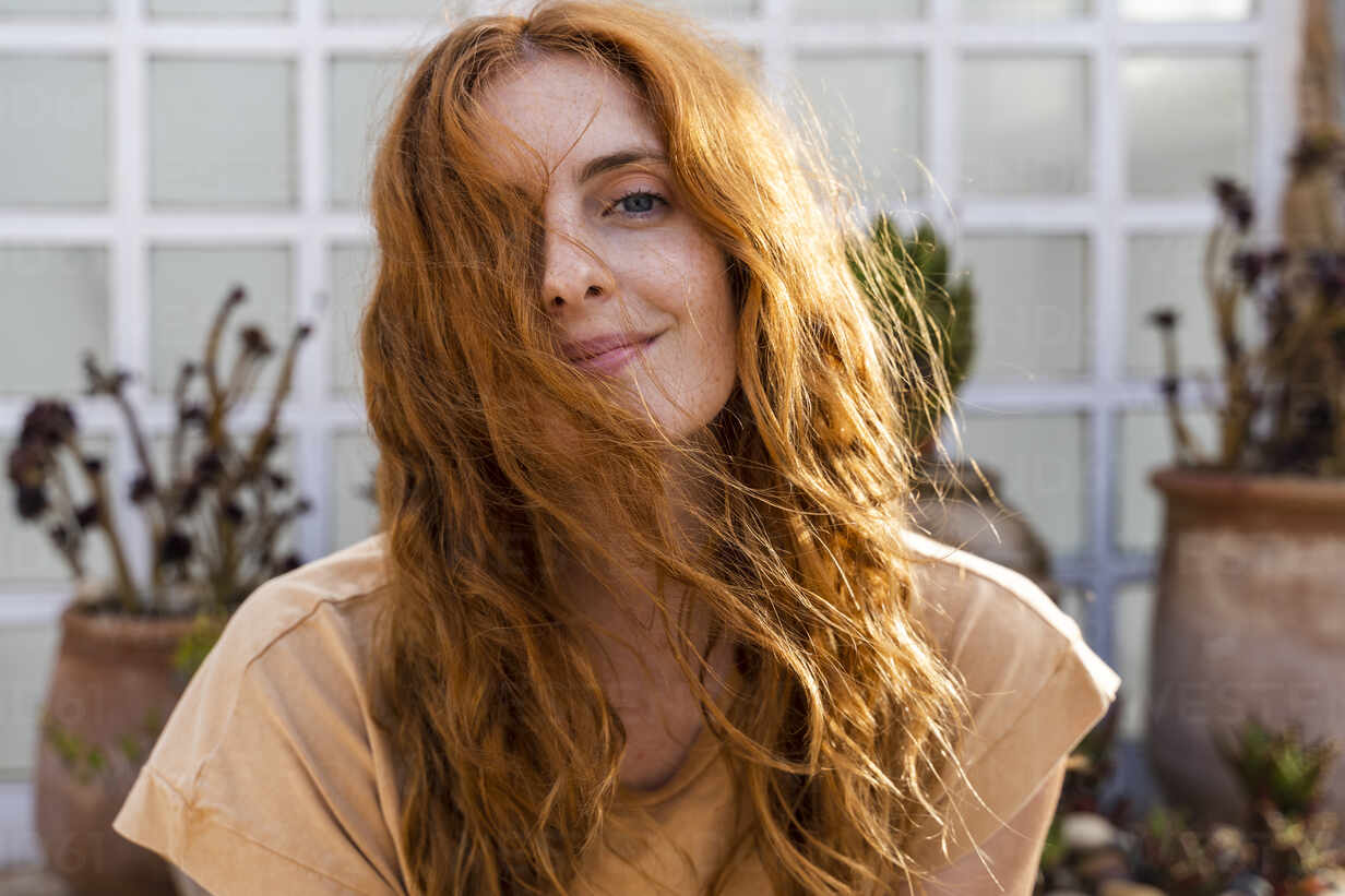 Portrait of smiling redheaded young woman on terrace - AFVF03957 - VITTA GALLERY/Westend61