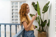Smiling redheaded young woman leaning against railing looking at cell phone - AFVF03960