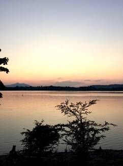Scenic view of Forggensee lake against sky during sunset at Ostallgaeu, Germany - JTF01328