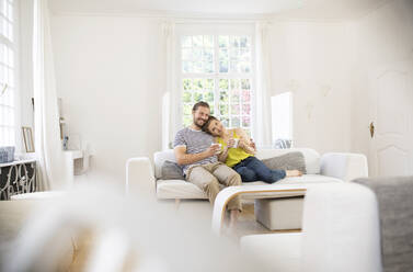 Happy young couple sitting on couch at home - MJFKF00001