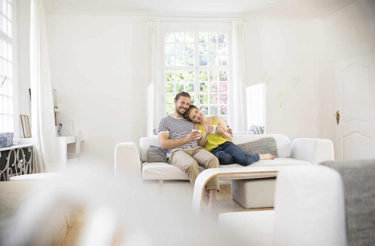Happy young couple sitting on couch at home - MJFKF00001 - MiJo/Westend61