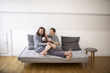 Happy young couple in pyjamas on bed couch at home - MJFKF00013