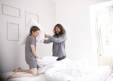 Playful young couple having a pillow fight at home - MJFKF00019
