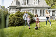 Happy extended family playing football in garden - MJFKF00037