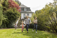 Happy extended family running in garden of their home - MJFKF00040