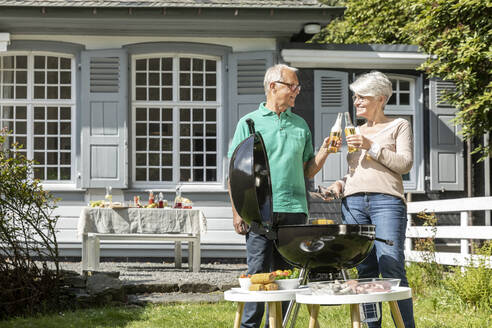Happy senior couple having a barbecue in garden of their home toasting with beer bottles - MJFKF00046