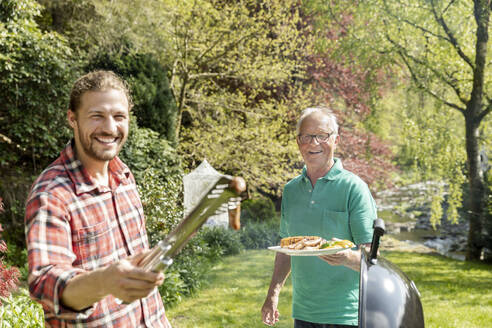 Portrait of happy man on a family barbecue in garden - MJFKF00052
