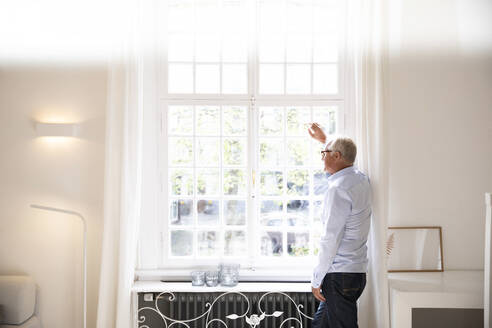 Senior man looking out of window at home - MJFKF00058
