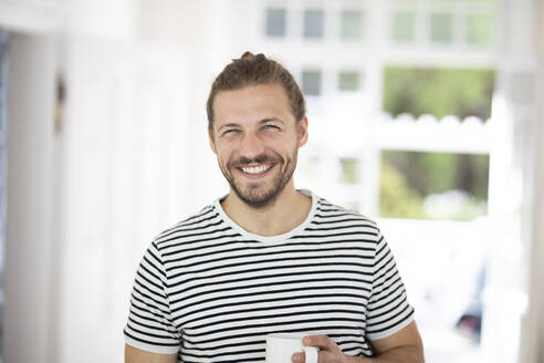 Portrait of smiling young man holding cup of coffee at home - MJFKF00061