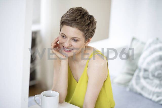 Smiling woman with cup of coffee at home - MJFKF00064 - MiJo/Westend61