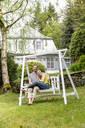 Happy couple relaxing in garden of their home - MJFKF00079