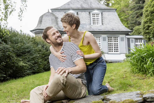 Happy woman embracing man on a wall in garden of their home - MJFKF00082