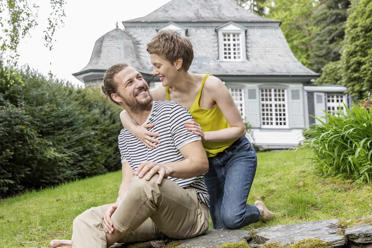 Happy woman embracing man on a wall in garden of their home - MJFKF00082 - MiJo/Westend61