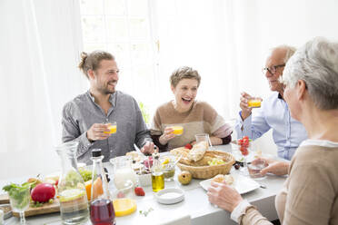 Happy senior couple with adult children having lunch at home - MJFKF00121