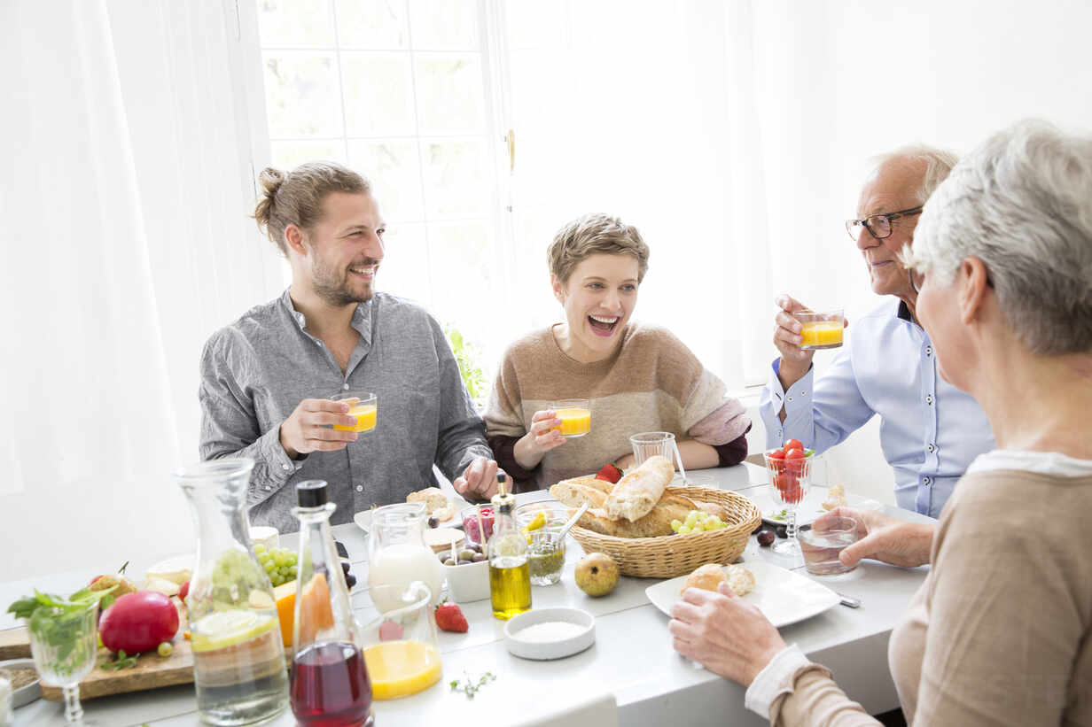 Happy senior couple with adult children having lunch at home - MJFKF00121 - MiJo/Westend61