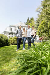 Happy senior couple with adult children standing in garden of their home - MJFKF00127