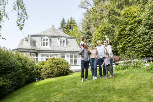 Happy extended family standing in garden of their home - MJFKF00130